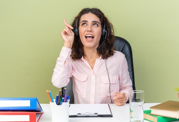 Überraschte hübsche kaukasische call-center-betreiberin auf kopfhörern, die am schreibtisch sitzen und bürowerkzeuge einzeln auf grüner wand suchen und zeigen?