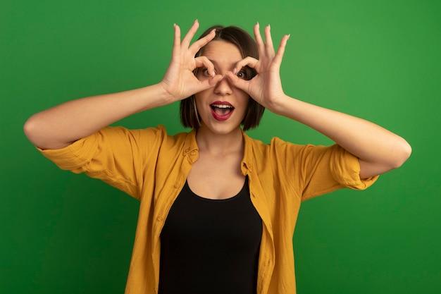 Überraschte hübsche kaukasische frau betrachtet kamera durch finger auf grün