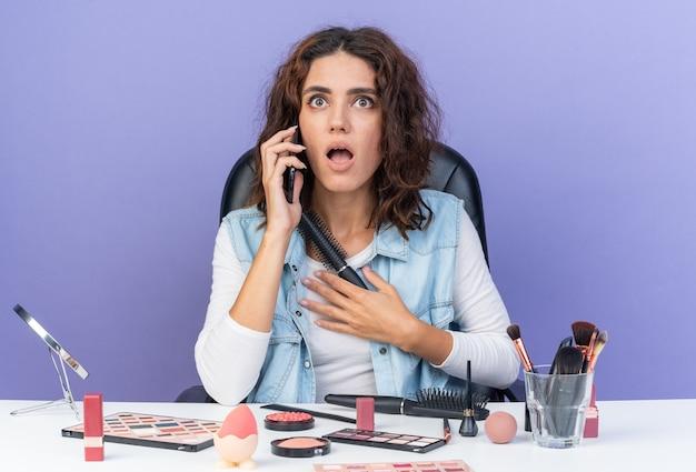Überraschte hübsche kaukasische frau, die am tisch mit make-up-tools sitzt, die am telefon spricht und die hand auf ihre brust legt, die den kamm isoliert auf der lila wand mit kopienraum hält