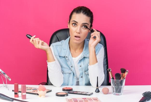 Überraschte hübsche kaukasische frau, die am tisch mit make-up-tools sitzt, die eyeliner auftragen