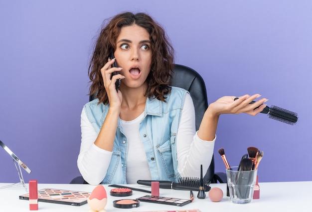 Überraschte hübsche kaukasische frau, die am tisch mit make-up-tools sitzt und am telefon spricht und einen kamm hält, der auf die seite schaut