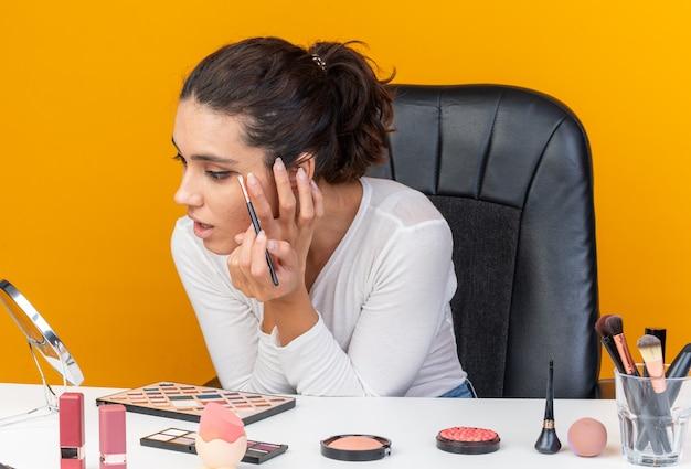 Überraschte hübsche kaukasische frau, die am tisch mit make-up-tools sitzt und lidschatten mit make-up-pinsel auf den spiegel aufträgt