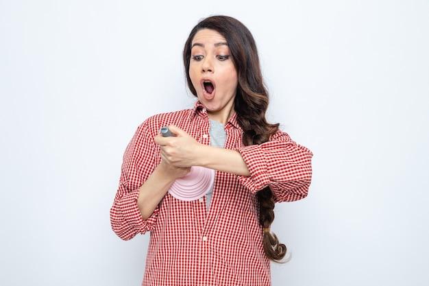 Überraschte hübsche kaukasische putzfrau, die den gummikolben auf ihrer brust hält und anschaut