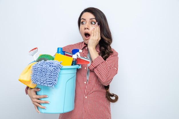 Überraschte hübsche kaukasische putzfrau, die reinigungsgeräte hält und auf die seite schaut