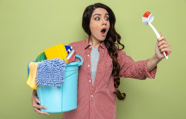 Überraschte hübsche kaukasische putzfrau, die reinigungsgeräte hält und bürste anschaut