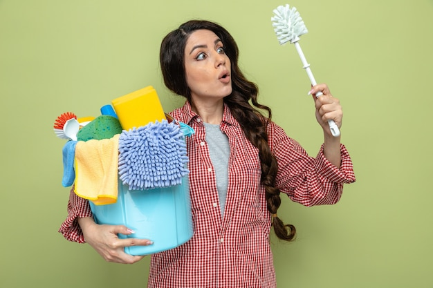 Überraschte hübsche kaukasische putzfrau, die reinigungsgeräte hält und toilettenbürste anschaut