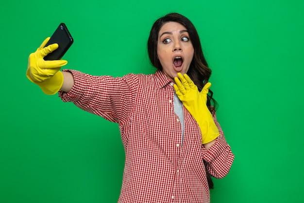 Überraschte hübsche kaukasische putzfrau mit gummihandschuhen, die das telefon hält und ansieht und die hand auf ihr kinn legt