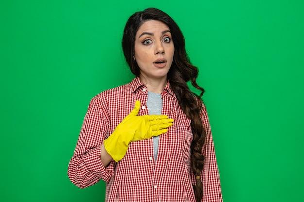 Überraschte hübsche kaukasische putzfrau mit gummihandschuhen, die hand auf ihre brust legt und