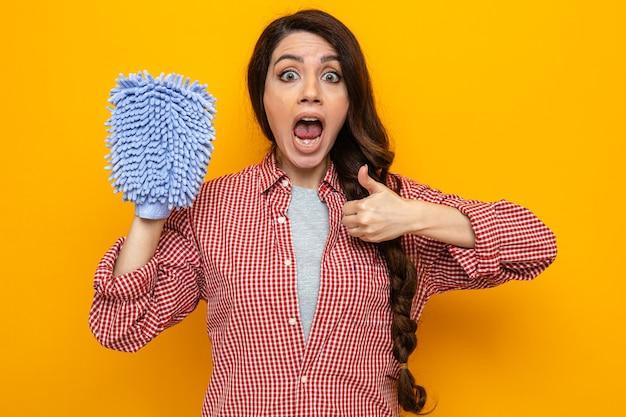 Überraschte hübsche kaukasische putzfrau mit mikrofaserhandschuh und daumen hoch