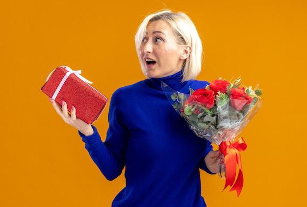 Überraschte hübsche slawische frau mit blumenstrauß und geschenkbox, die am valentinstag auf die seite schaut