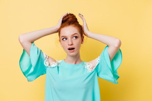 Überraschte ingwerfrau im kleid korrigiert haarschwanz und schaut weg