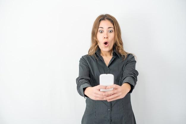 Überraschte isolierte schöne junge frau, die smartphone mit augen und mund weit offen schaut