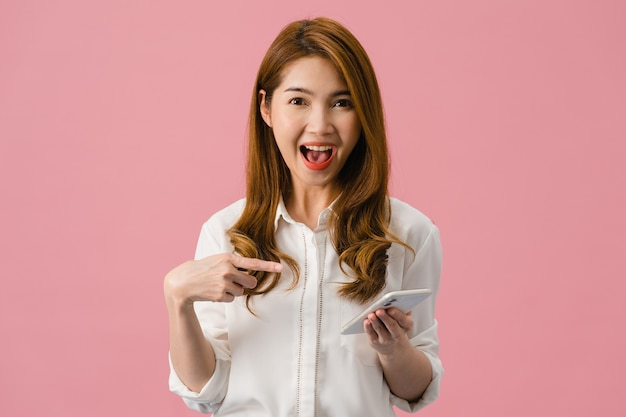 Überraschte junge asiatin, die handy mit positivem ausdruck benutzt, breit lächelt, in freizeitkleidung gekleidet ist und die kamera auf rosafarbenem hintergrund betrachtet.