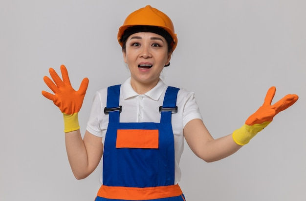 Überraschte junge asiatische baumeisterin mit orangefarbenem schutzhelm und sicherheitshandschuhen, die die hände offen halten