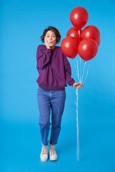 Überraschte junge attraktive frau mit lässiger frisur, die bündel von heliumballons hält