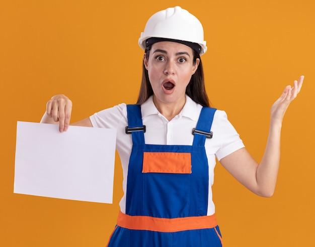 Überraschte junge baumeisterfrau in uniform, die papierverbreitungshand lokalisiert auf orange wand hält
