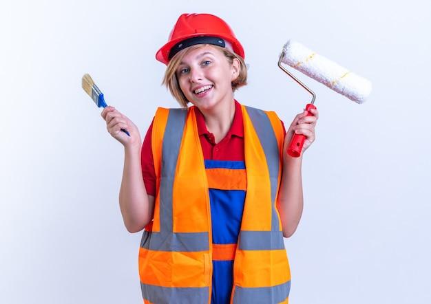 Überraschte junge baumeisterin in uniform, die walzenbürste mit pinsel isoliert auf weißer wand hält