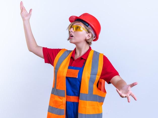 Überraschte junge baumeisterin in uniform mit brille, die die hände auf weißem hintergrund ausbreitet
