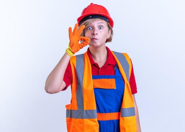 Überraschte junge baumeisterin in uniform mit handschuhen, die stillegeste isoliert auf weißer wand zeigt?