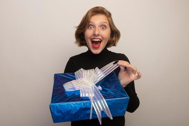 Überraschte junge blonde frau mit geschenkpaket