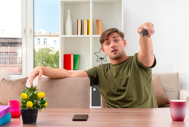Überraschte junge blonde hübsche mann sitzt am tisch und hält tv-fernbedienung mit blick auf die kamera im wohnzimmer