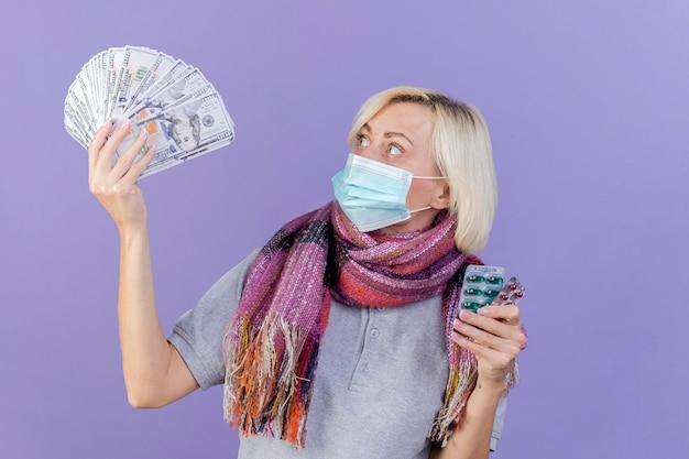 Überraschte junge blonde kranke slawische frau, die medizinische maske und schal trägt