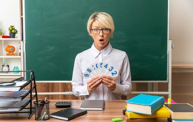 Überraschte junge blonde lehrerin mit brille, die am schreibtisch mit schulwerkzeugen im klassenzimmer sitzt und zahlenfans zeigt
