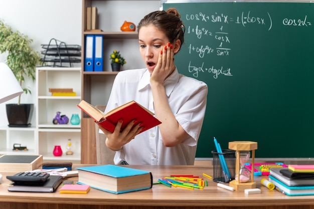 Überraschte junge blonde mathematiklehrerin, die am schreibtisch mit schulwerkzeugen sitzt und ein buch liest, das im klassenzimmer die hand aufs gesicht hält