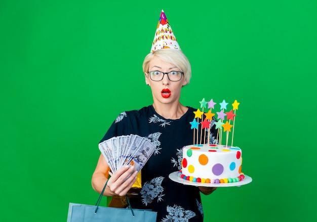 Überraschte junge blonde partyfrau, die brille und geburtstagskappe hält, die geburtstagstorte mit sternengeld-geschenkbox und papiertüte hält, die front lokal auf grüner wand mit kopienraum betrachten