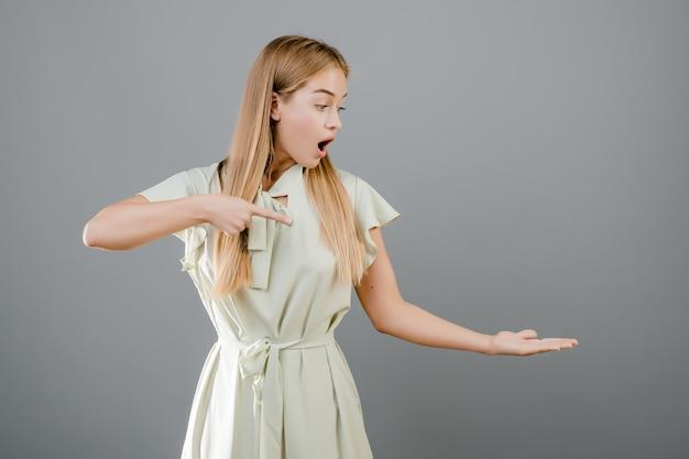 Überraschte junge blondine, die finger auf copyspace auf ihrer hand lokalisiert über grau zeigen