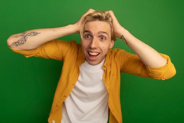 Überraschte junge blondine, die gelbes t-shirt trägt, packte den kopf isoliert auf grün