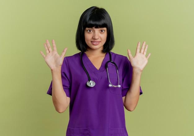 Überraschte junge brünette ärztin in uniform mit stethoskop steht mit erhobenen händen lokalisiert auf olivgrünem hintergrund mit kopienraum