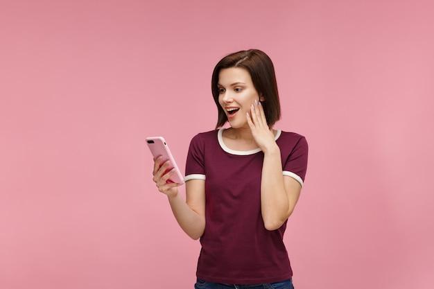 Überraschte junge brünette frau, die rosa smartphone hält,
