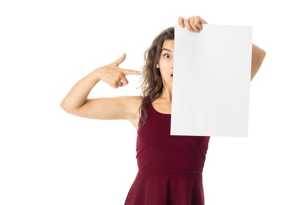 Überraschte junge brünette frau im roten kleid mit weißem plakat in den händen lokalisiert