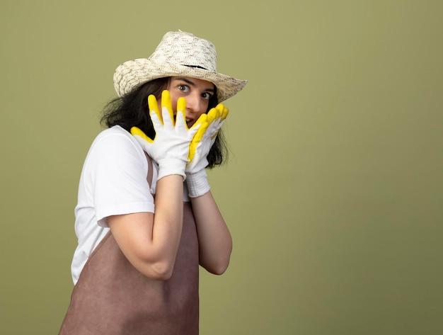 Überraschte junge brünette gärtnerin in uniform, die gartenhut und handschuhe trägt, legt hände