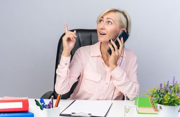 Überraschte junge callcenter-betreiberin mit headset am tisch sitzend mit bürowerkzeugen nach oben