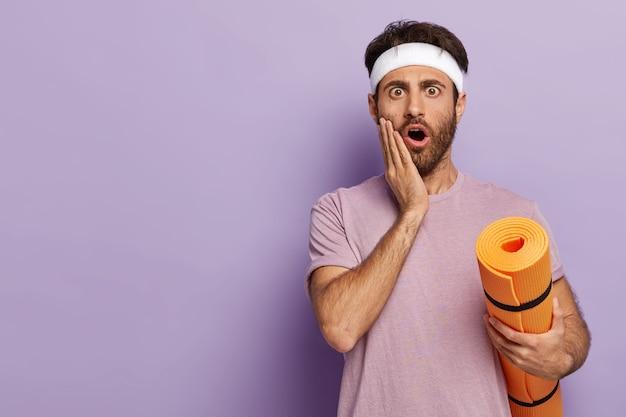 Überraschte junge fitness-mann hält aufgerollte trainingsmatte, trägt weißes stirnband und lässiges t-shirt, schockiert, etwas für das training zu vergessen