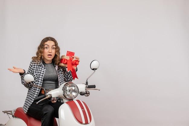 Überraschte junge frau auf moped, die geschenk und karte auf grau hält