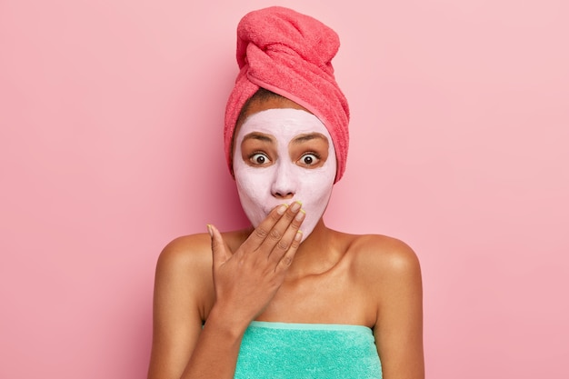 Überraschte junge frau bedeckt mund mit handfläche, schaut sich im spiegel an, trägt gesichtsmaske aus ton auf, um jünger und erfrischt auszusehen, steht in handtuch gewickelt, isoliert über rosa wand