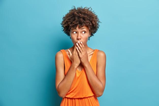 Überraschte junge frau bedeckt mund starrt beeindruckt hört geheimnisse trägt orangefarbenes kleid, das von etwas geschockt wird, das an der blauen wand posiert