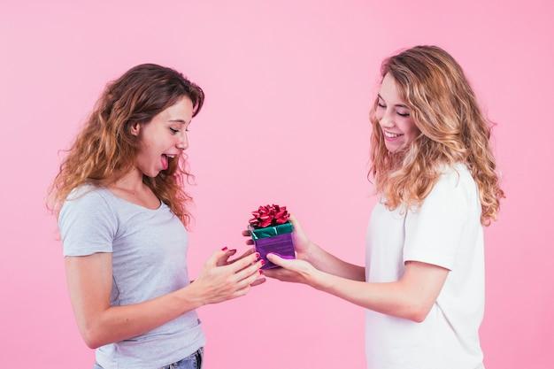Überraschte junge frau, die geschenk von ihrem freund gegen rosa hintergrund nimmt