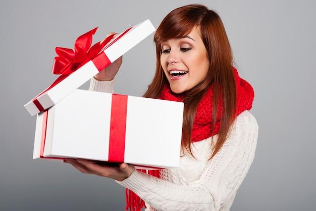 Überraschte junge frau, die in das weihnachtsgeschenk späht