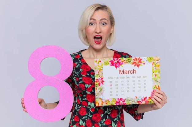 Überraschte junge frau, die kalender des monats märz und nummer acht hält und internationalen frauentagsmarsch feiert