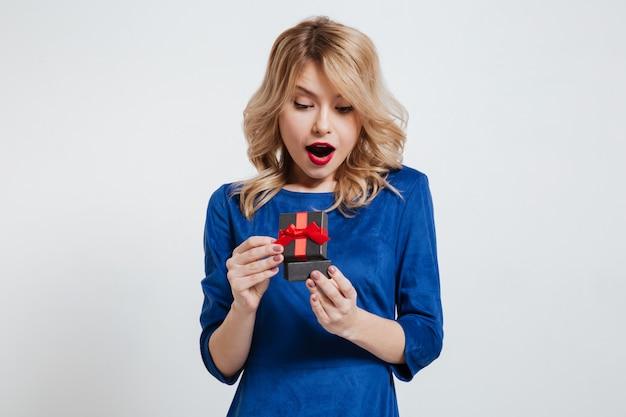 Überraschte junge frau, die kleine geschenkbox hält