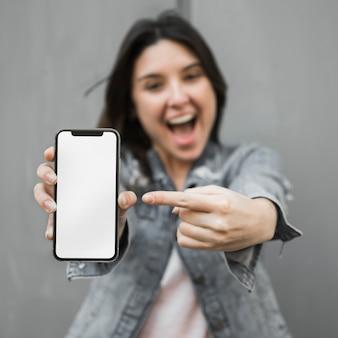 Überraschte junge frau, die smartphone zeigt