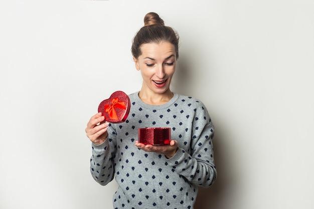 Überraschte junge frau freut sich mit einem geschenk auf hellem hintergrund. valentinstag, geburtstag. banner.