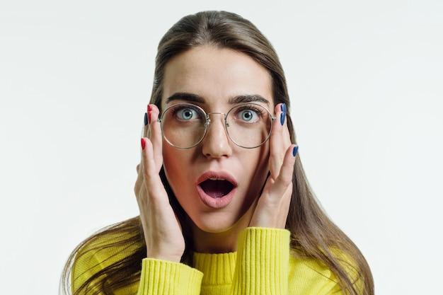 Überraschte junge frau in der gelben strickjacke