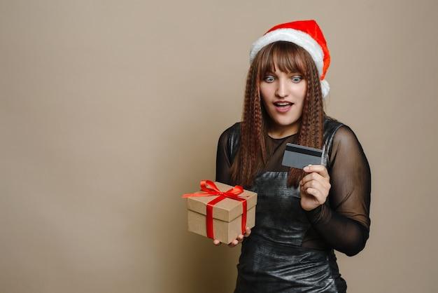 Überraschte junge frau in der weihnachtsmütze, die ein weihnachtsgeschenk mit kreditkarte hält