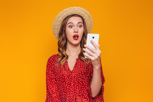 Überraschte junge frau in einem roten kleid und einem strohhut hält ein handy und liest eine sms-nachricht macht online-einkäufe isoliert auf orange wand. sommermädchen mit zelle online-shopping-konzept