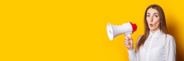 Überraschte junge frau in einem weißen hemd hält ein megaphon auf einem gelben hintergrund